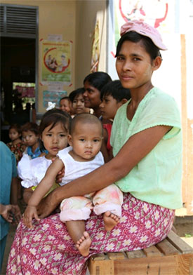 Mothers and children waiting outside a clinic to receive measles vaccine. Photo credit: C. McNab/Measles Initiative