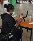 A masked Ethiopian worker prepares a measles vaccination shot.