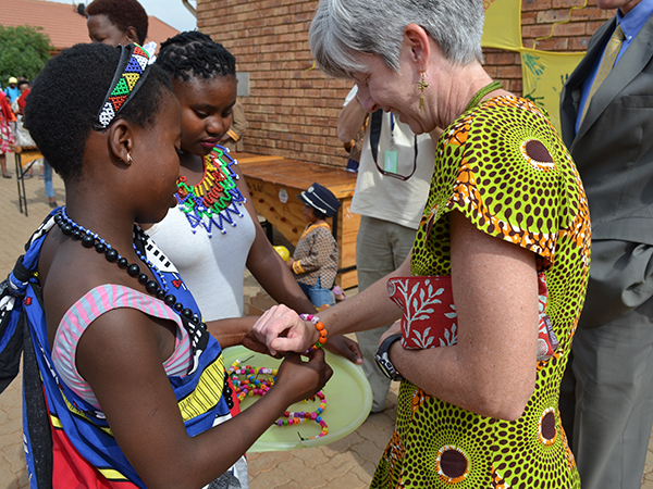 "Dr. Nancy Knight receives a ""welcome"" bracelet from children, caregivers, and site staff, at CDC-funded orphans and vulnerable children (OVC) site, Sithandizingane, in Ekurhuleni, Gauteng, Friday October 2, 2015."