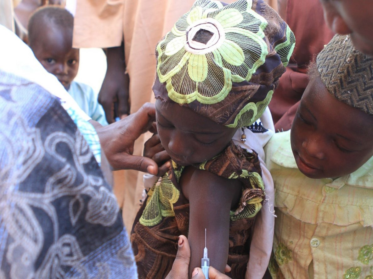 In Nigeria, a little girl prepares to receive her measles vaccination while other children watch.