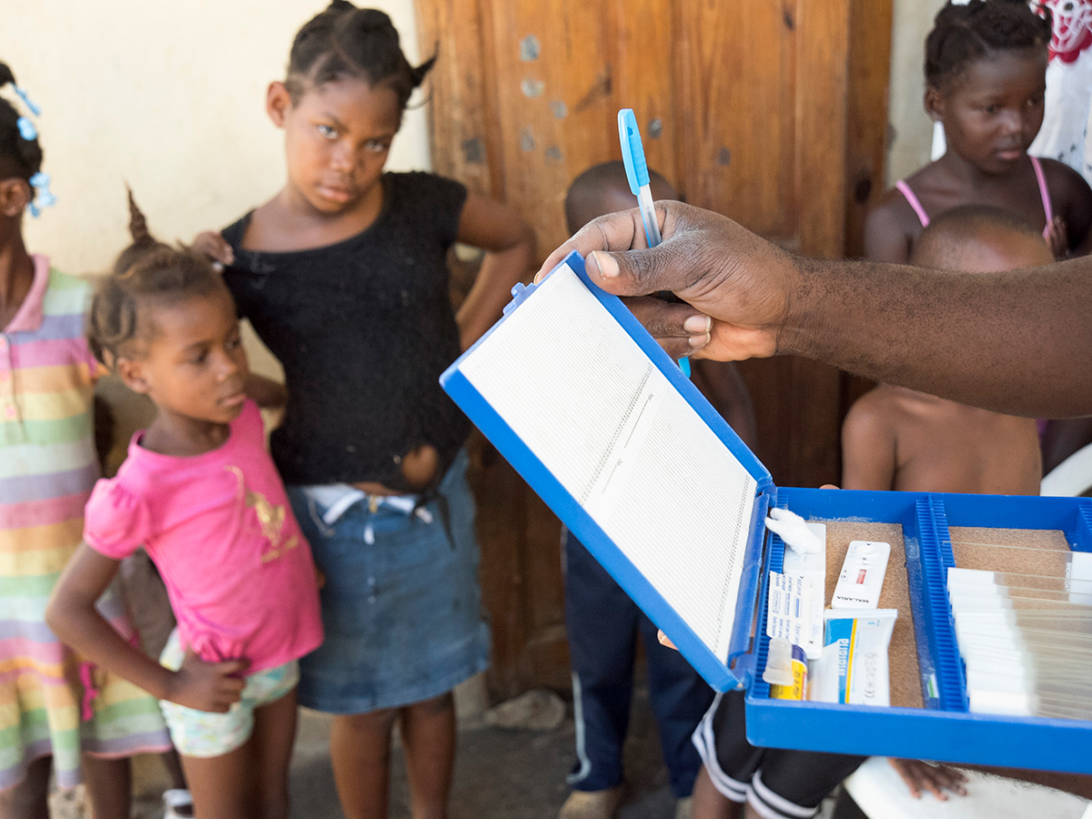 A community health worker in Haiti prepares to conduct Rapid Diagnostic Tests integrated with screening for lymphatic fillariasis.
