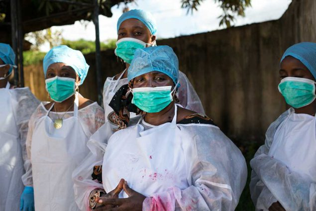 Public health workers learn how to use personal protective equipment at a CDC facilitated training in Guinea. (Photo credit: Patrick Adams/RTI International)