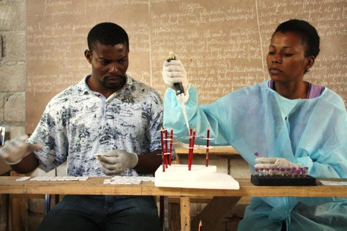 In this image, created in February, 2015, by Centers for Disease Control and Prevention (CDC) Epidemic Intelligence Service (EIS) Officer, Alaine Kathryn Knipes, Ph.D., two laboratory technicians with Haiti's ministry of health (MoH), Mr. Dorelus and Mrs. Byzette, were processing blood samples in order to test for lymphatic filariasis (LF) and malaria, using rapid diagnostic tests in a rural classroom located in the Nippes Department of Haiti. This was one of the entries in the 2015 CDC Connects, Public Health in Action Photo Contest.