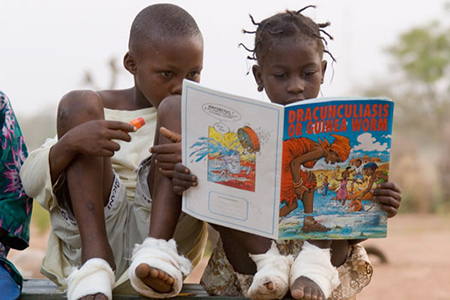 While at the containment center in Ghana two children look at a picture book about Guinea worm disease. Credit: The Carter Center