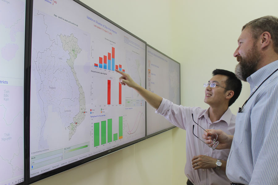 A photo of the data dashboard with Dr. Tran and Peter Rzeszotarski, CDC Emergency Management Specialist.