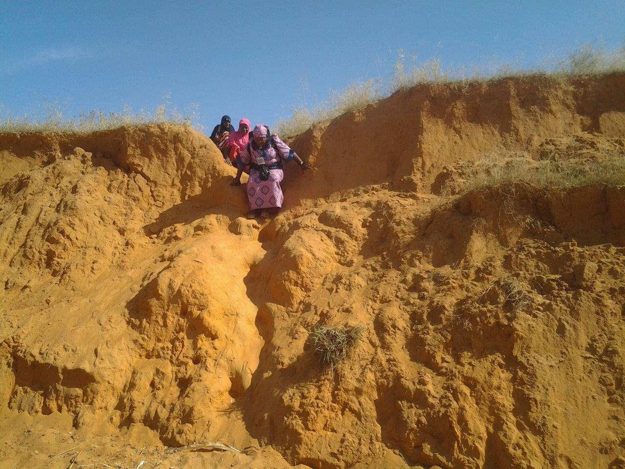 A Nigeria FETP resident and two data collectors hike down extremely difficult terrain to reach underserved settlements.