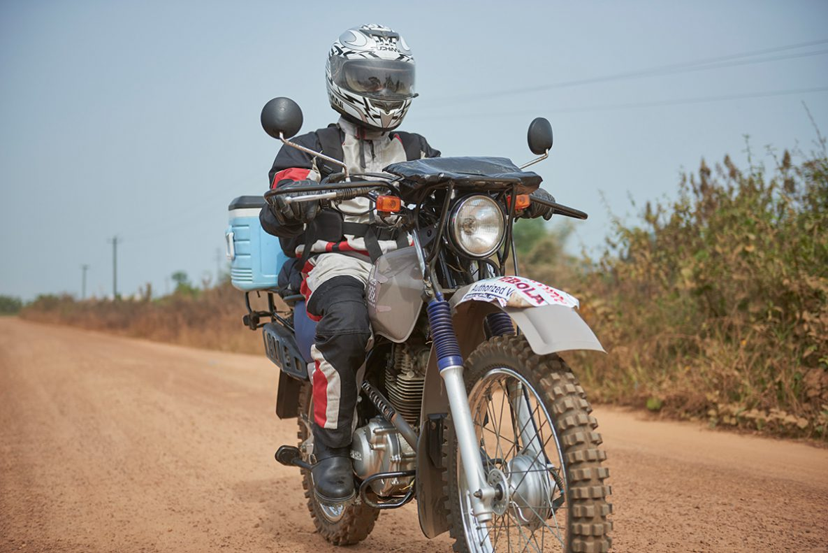 A motorcycle courier delivers laboratory samples over rough roads in Liberia.