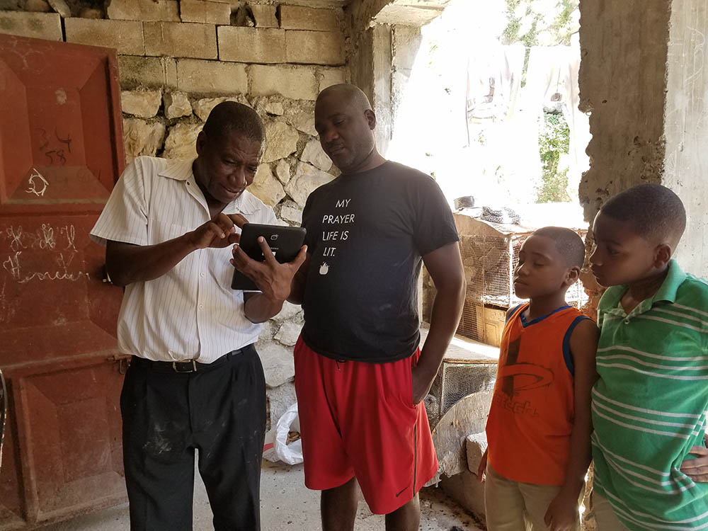 From the Haiti pilot. The vector surveillance technician (L. Balthazar, holding the tablet) using the app to collect demographic information from the head of the household. Once community members saw how he entered their information into the app, they were eager to participate and volunteer their households for vector surveillance.