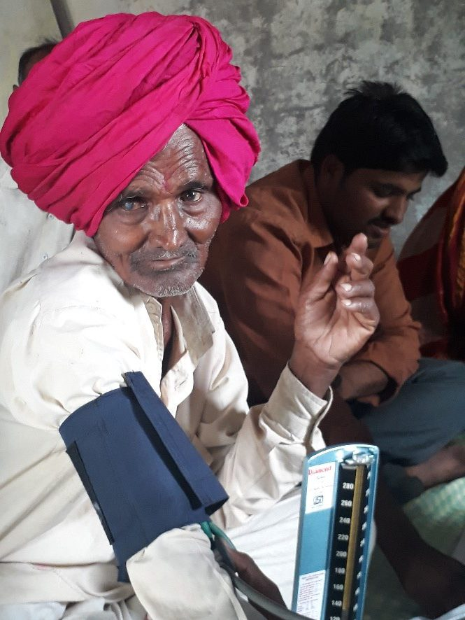 An elderly man with cataracts is screened for hypertension for the first time during May Measurement Month 2017. Research suggests a possible link between untreated hypertension and cataracts. Photo credit: Dr. Arun More