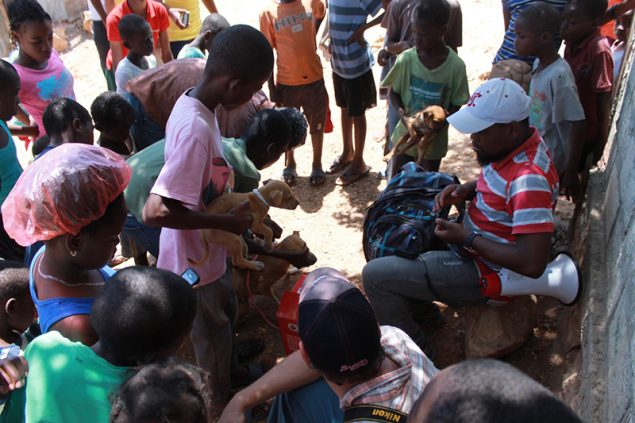 Children bring their dogs to vaccination post in Haiti.