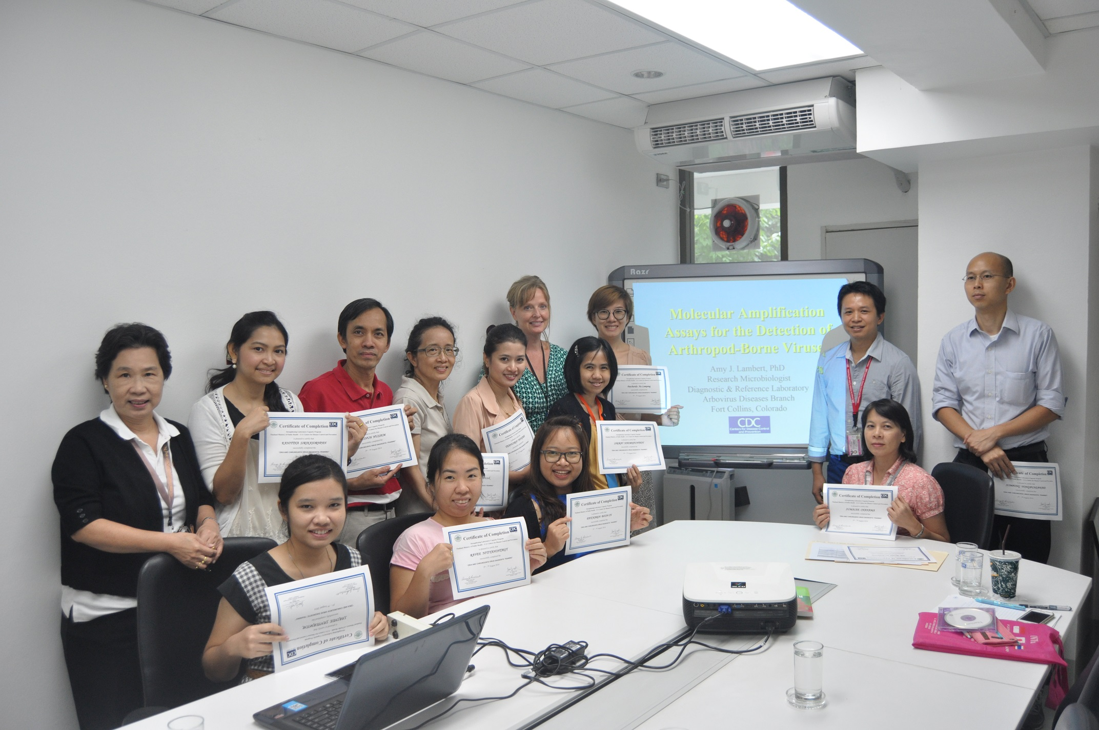 Laboratory workers from the National Institute of Health and Chulalongkorn University display certificates after successfully completing a training on how to identify Zika and Chikungunya viruses.