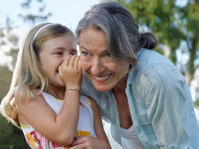 Young girl whispering into elderly women's ear