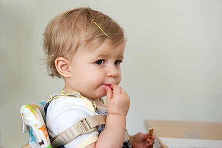 Toddler girl eating at a table
