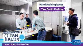 A man with a suitcase washing his hands in a bathroom and a reminder that handwashing keeps your family healthy.
