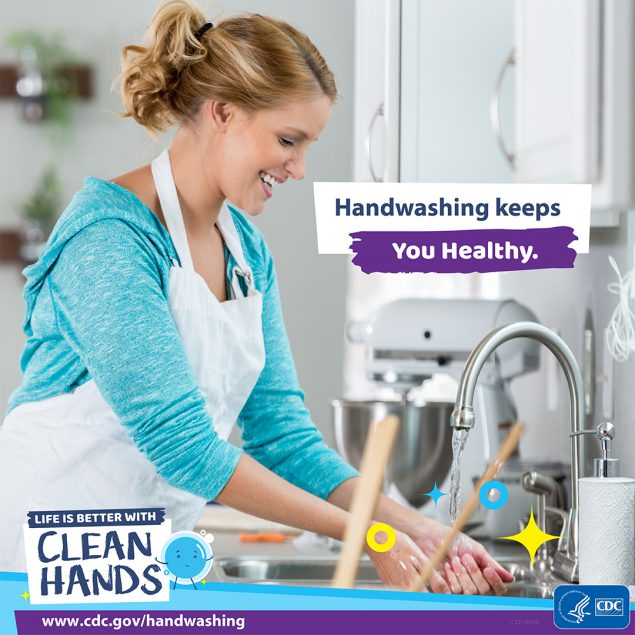 A woman washing hands in her kitchen.