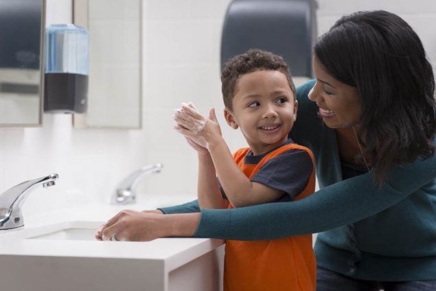 mom helping toddler boy wash his hands in a public restroom
