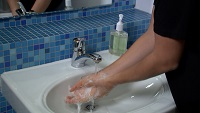 man washing his hands with soap and water