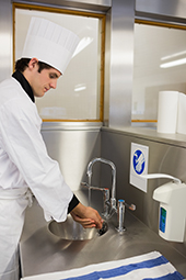 a food service worker or chef washing his hands at a basin