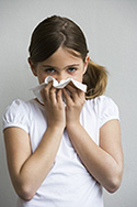 girl wiping nose after sneezing