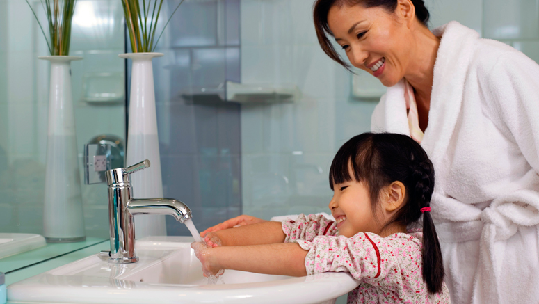 mother helping daughter wash her hands at sink