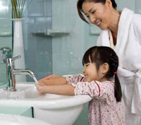 A mother instructing a child to wash her hands