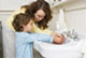 mom helping boy wash hands at sink