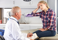 photo: girl with head pain talking to a doctor