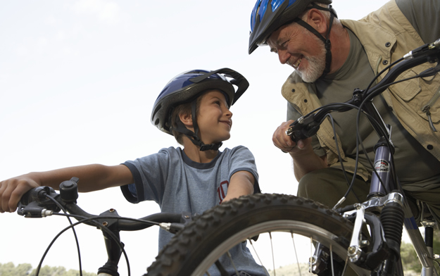 photo: father and son riding bikes with helmets