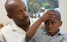 African American boy with holding his forehead while sitting on his father's lap