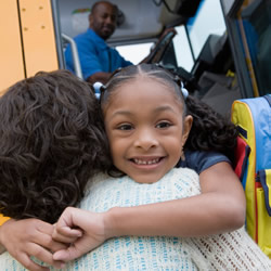 Photo: Girl hugging her Mom by the school bus