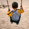 Photo of a boy on a swing over sand