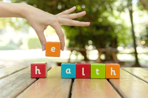 Colorful building blocks spelling the word health and representing health communication basics.