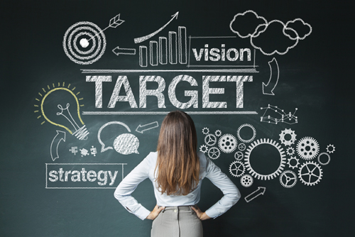 Women standing in front of black board with the words Target in large white letters and vision, strategy in small white letter.