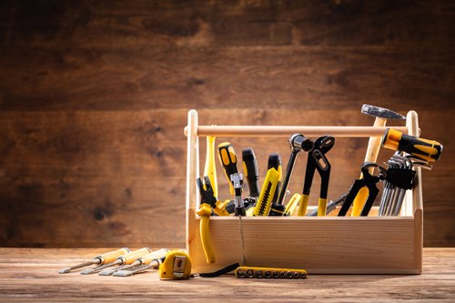 Wooden toolbox containing basic tools such as screwdriver, hammer, wrench, pliers