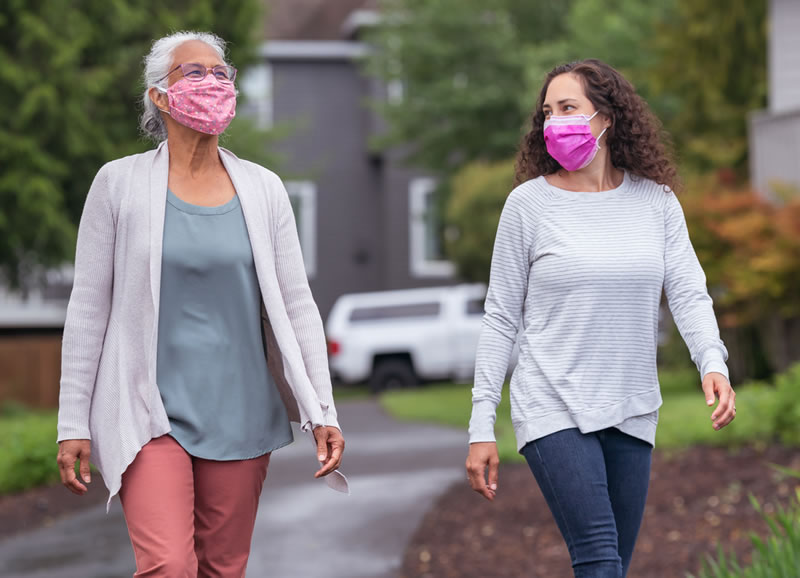 two women wearing face coverings walking outside