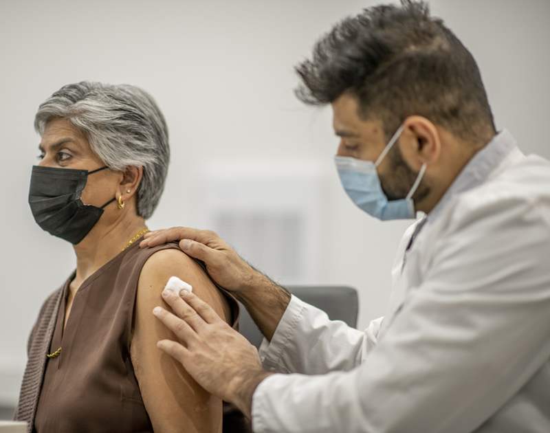 woman wearing face mask getting vaccine