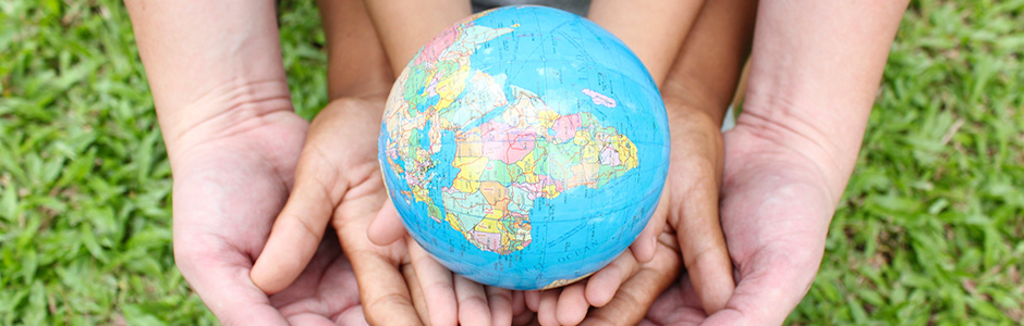 Kids hands holding a small globe