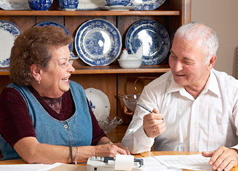 Elderly couple reviewing documents.