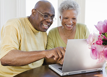 Two older adults looking at a computer.