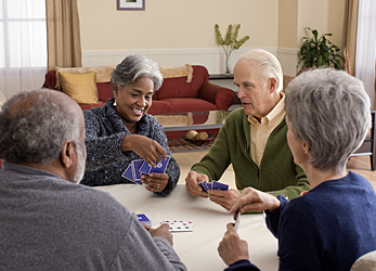 Photo of elderly adults playing cards