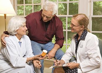 Senior couple discussing medication with a care physician.