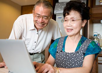 Photo of an elderly couple looking at a laptop computer