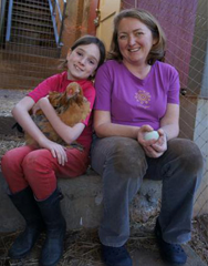 Mother and Daughter sit and hold a chicken