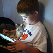 Boy sits with kitten while he looks at iPad.