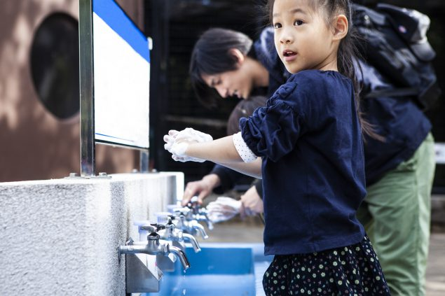 Girl washing hands in sink after touching animal