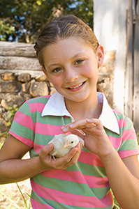 A girl holds a chick. Photo