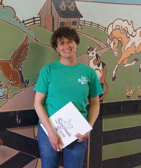 Dena Little standing in front of a mural