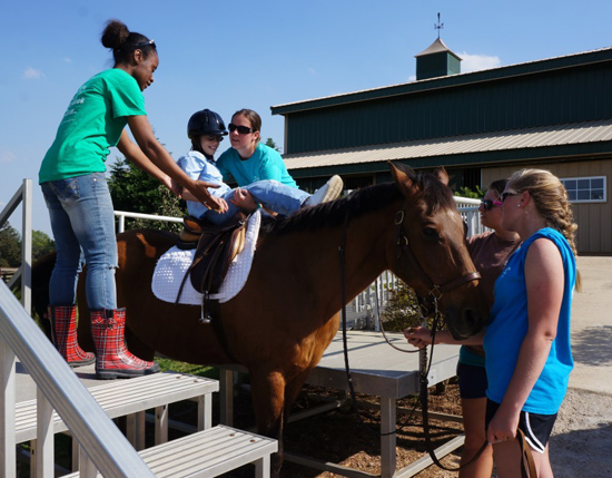 Group of volunteers helping a child onto a horse
