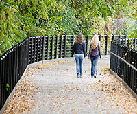 2 women walking on a park path