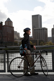man with bicycle looking at skyline over river